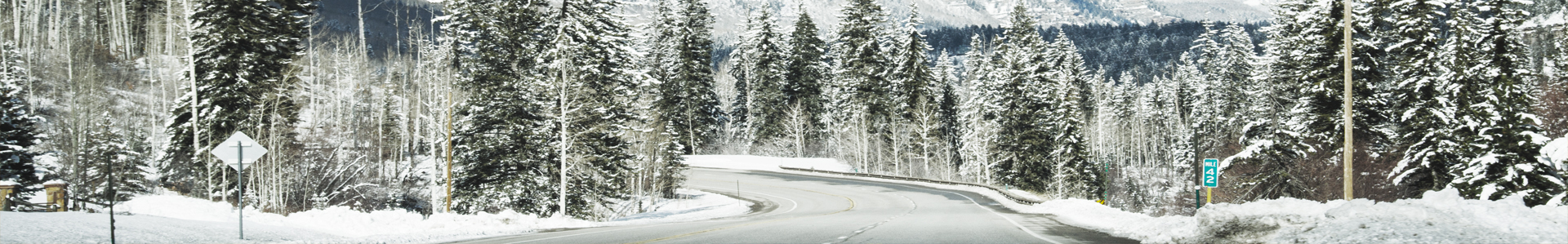 Winter road winding through mountain forest